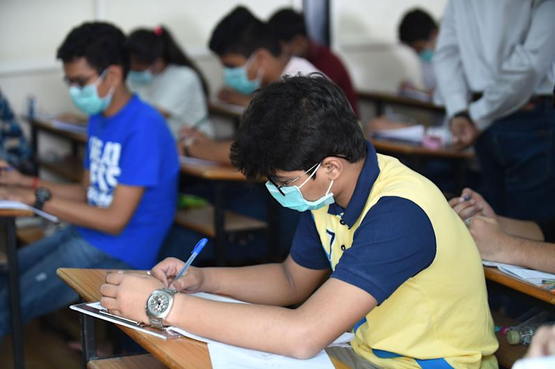 Students sit for the Gujarat Board Xth examination as they wear facemasks provided by the school management at Sadhana Vinay Mandir school, following the COVID-19 coronavirus outbreak, in Ahmedabad on March 5, 2020. - More than 95,000 people have been infected and over 3,200 have died worldwide from the new coronavirus, which by on March 5 had reached some 80 countries and territories. (Photo by SAM PANTHAKY / AFP) (Photo by SAM PANTHAKY/AFP via Getty Images)