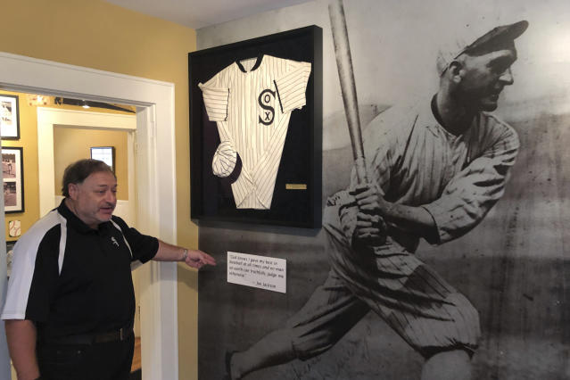 In this Sept. 29, 2019, photo, Michael Wallach, managing director of the Shoeless Joe Jackson Museum, looks at replica of a Joe Jackson jersey in Greenville, S.C. (AP Photo/Paul Newberry)