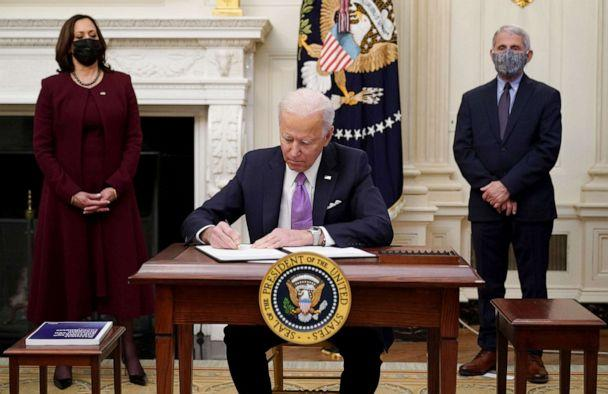 PHOTO: President Joe Biden signs executive orders as part of the Covid-19 response as US Vice President Kamala Harris and Director of NIAID Anthony Fauci look on in the State Dining Room of the White House, on Jan. 21, 2021. (Mandel Ngan/AFP via Getty Images)