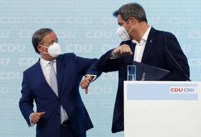 Christian Democratic Union (CDU) chairman Armin Laschet, left, and Christian Social Union (CSU) chairman Markus Soeder, right, bump elbows during a press conference in Berlin, Germany, Monday, June 21, 2021. (Michele Tantussi/Pool Photo via AP)