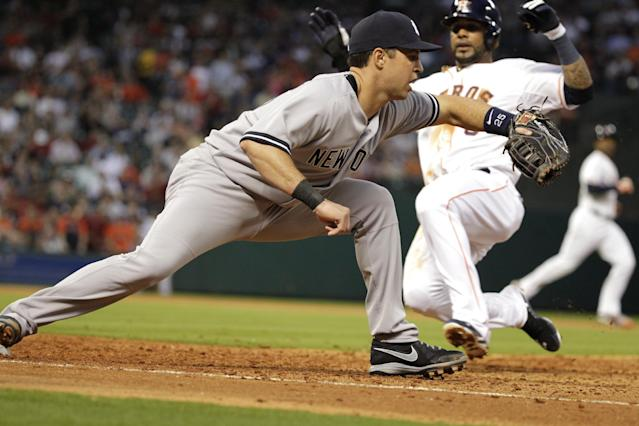 New York Yankees first baseman Mark Teixeira doubles off Houston Astros' Jonathan Villar at first after a fly out by Robbie Grossman in the fourth inning of a baseball game, Tuesday, April 1, 2014, in Houston. Houston won 6-2. (AP Photo/Patric Schneider)