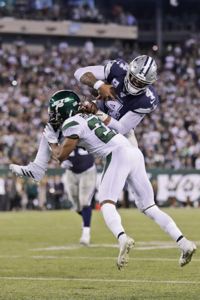 Dallas Cowboys quarterback Dak Prescott, top, tries to leap New York Jets' Darryl Roberts during the second half of an NFL football game, Sunday, Oct. 13, 2019, in East Rutherford, N.J. (AP Photo/Adam Hunger)