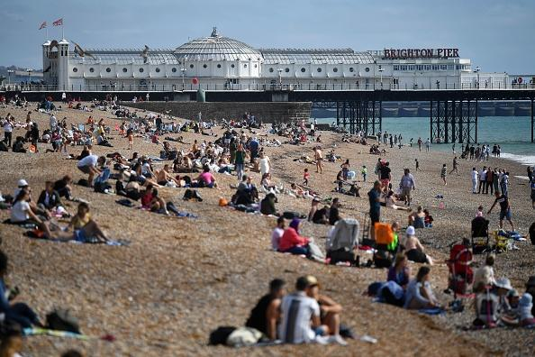 Beachgoers pack the beach in Brighton in the late summer sunshine, on the south coast of England.