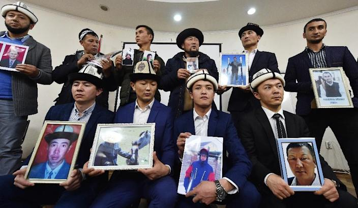 """Kyrgyz family members hold portraits of their relatives who they fear are being held in notorious """"re-education camps"""" in China's Xinjiang region (AFP Photo/Vyacheslav OSELEDKO)"""