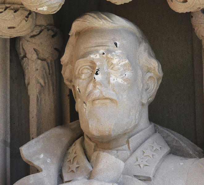 FILE - In this Aug. 17, 2017 file photo, the defaced Gen. Robert E. Lee statue stands at the Duke Chapel on Thursday, Aug. 17 2017, in Durham, N.C. Duke University removed a statue of Gen. Robert E. Lee early Saturday, Aug. 19, days after it was vandalized amid a national debate about monuments to the Confederacy. The university said it removed the carved limestone likeness early Saturday morning from Duke Chapel where it stood among 10 historical figures depicted in the entryway (Bernard Thomas/The Herald-Sun via AP)