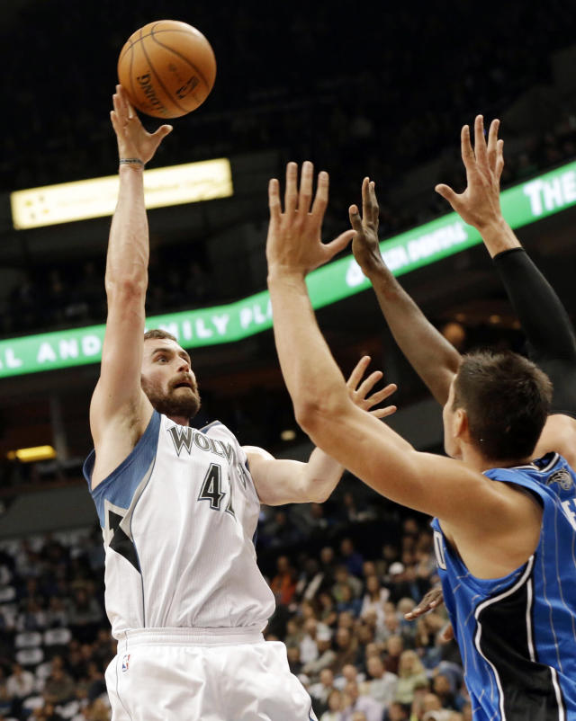 Minnesota Timberwolves' Kevin Love, left, shoots Orlando Magic' Nikola Vucevic, of Montenegro, in the first quarter of an NBA basketball game, Wednesday, Oct. 30, 2013 in Minneapolis. (AP Photo/Jim Mone)