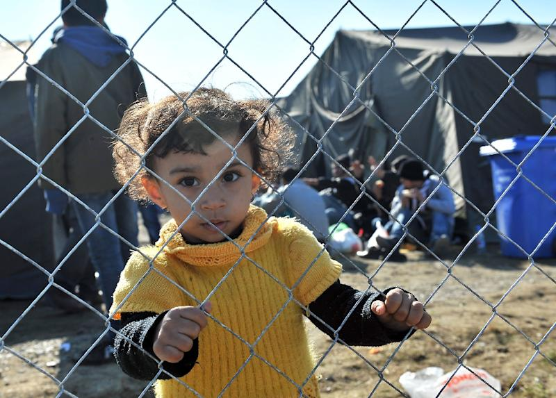 A girl holds on to a fence at a transit camp housing migrants and refugees in Slavonski Brod on November 4, 2015 (AFP Photo/Elvis Barukcic)
