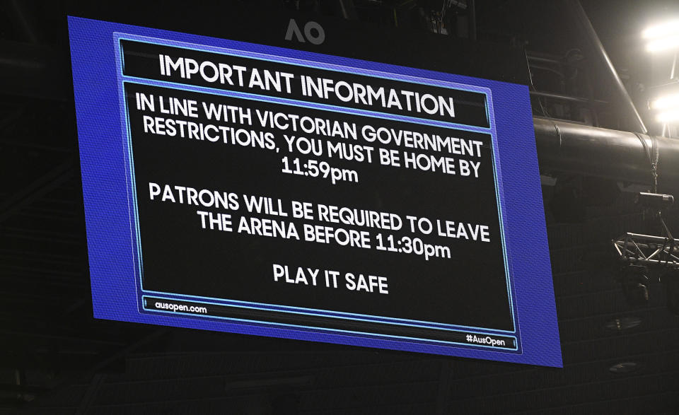 An electronic signboard on Rod Laver Arena reminds patrons about the lockdown start time during the third round match between Serbia's Novak Djokovic and United States' Talyor Fritz at the Australian Open tennis championship in Melbourne, Australia, Friday, Feb. 12, 2021. Melbourne, Australia's second-largest city, will begin its third lockdown on Friday due to a rapidly spreading COVID-19 cluster centered on hotel quarantine.(AP Photo/Andy Brownbill)