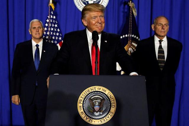 President Trump center, flanked by Vice President Mike Pence and Homeland Security Secretary John Kelly, takes the stage to deliver remarks at Homeland Security headquarters. (Photo: Jonathan Ernst/Reuters)