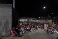 El Modena players rest in an open space due to COVID-19 restrictions during halftime of their high school football game with El Dorado in Orange, Calif., Friday, March 19, 2021. (AP Photo/Jae C. Hong)