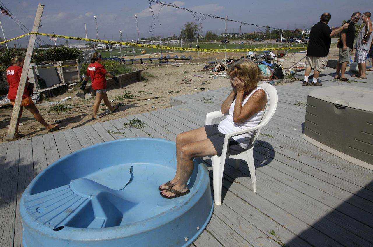 Overcome with emotion, cabana owner Janet Ryan sits on the porch at the Breezy Point Surf Club in the Queens borough of New York, Saturday, Sept. 8, 2012, after her cabana sustained damage when a severe weather storm passed through the area. A tornado swept out of the sea and hit the beachfront neighborhood in New York City, hurling debris in the air, knocking out power and startling residents who once thought of twisters as a Midwestern phenomenon. Firefighters were still assessing the damage, but no serious injuries were reported and the area affected by the storm appeared small. (AP Photo/Kathy Willens)