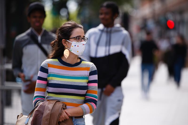A young woman wearing a face mask waits at a pedestrian crossing on Oxford Street in London, England, on June 20, 2020. Today has been the first Saturday of high street shopping since non-essential retail stores across England were allowed to reopen last week, having been closed under the coronavirus lockdown for nearly three months. Yesterday, monthly retail sales data from the UK's Office for National Statistics (ONS) revealed the beginnings of a rebound during May, with a 12 percent recovery from record falls in April, but sales nonetheless remained 13 percent below February's pre-pandemic total. Retail sales figures for June, taking into account this month's reopening of the sector, will be published by the ONS on July 24. (Photo by David Cliff/NurPhoto via Getty Images)
