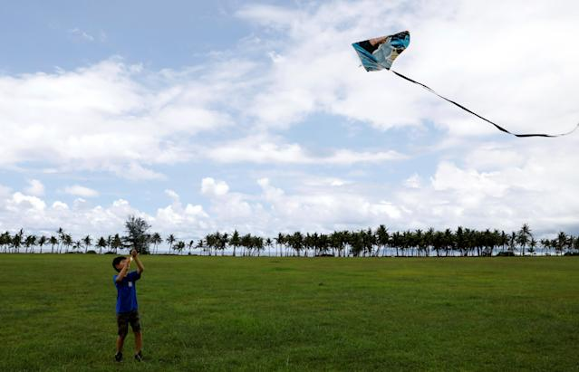 <p>A pupil flies his kite on the fields of Asan Memorial Park on the island of Guam, a U.S. Pacific Territory, August 11, 2017. (Erik De Castro/Reuters) </p>