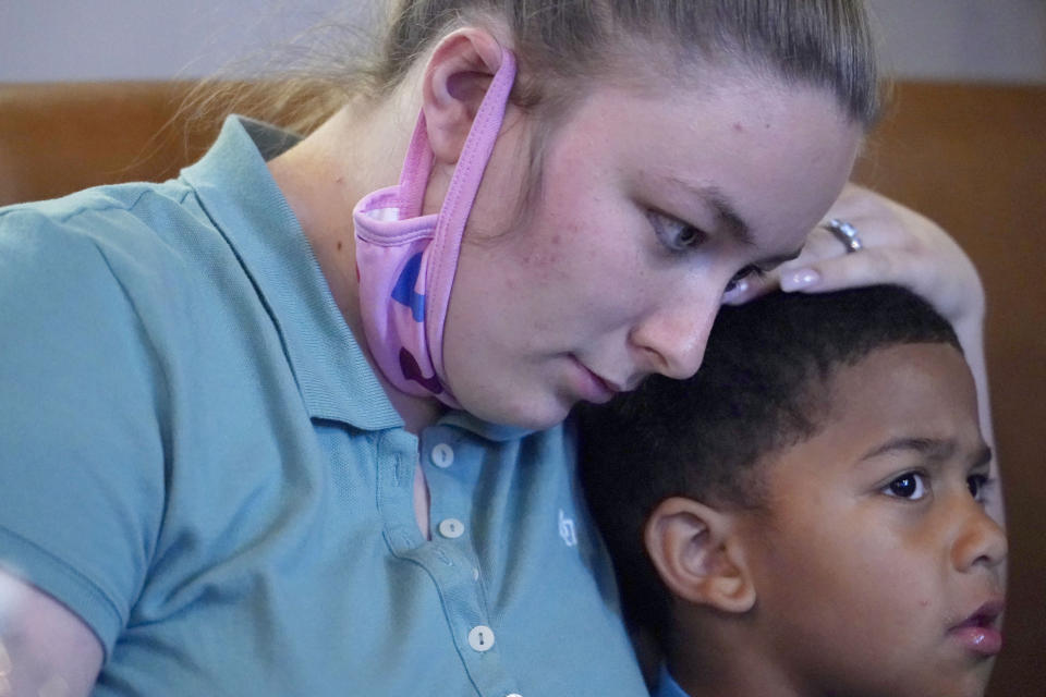 Alexis Rankin, hugs her oldest son, Peyton Lee, 5, as she recalls the events of the evening of February 8, 2018, when she and her on-again-off-again boyfriend Willie Jones Jr., argued while on their way to her stepfather's home in Scott County, Miss. Shortly after arriving, Jones, who is black, was discovered hanging from a tree in the yard of Rankin's family home. The sheriff's department and the Mississippi Bureau of Investigation, both ruled the death a suicide. However, a Jackson-area judge in April awarded close to $11.4 million to Jones' family in a civil suit claiming wrongful death, alleging that Rankin's stepfather, Harold O'Bryant, Jr., either killed Jones or failed to prevent him from killing himself. (AP Photo/Rogelio V. Solis)