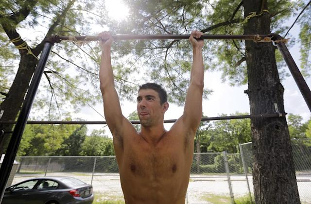 In this July 31, 2014 photo, Michael Phelps prepares to do pull-ups on a makeshift bar at Meadowbrook Aquatic and Fitness Center in Baltimore. This is where Phelps put in most of the work to become the most decorated athlete in Olympic history. This is where he's looking to add to that legacy after an aborted retirement, his eyes firmly on the Rio Games two years away. (AP Photo/Patrick Semansky)