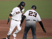 San Francisco Giants' Brandon Crawford, left, is congratulated by third base coach Ron Wotus as he runs the bases after hitting a solo home run against the San Diego Padres during the second inning of the first game of a baseball doubleheader Friday, Sept. 25, 2020, in San Francisco. (AP Photo/Tony Avelar)