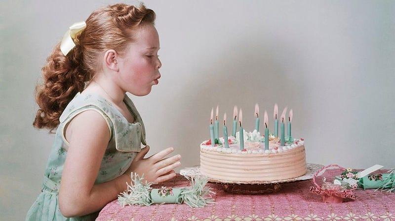 Colorized vintage photo of young girl blowing out candles on birthday cak