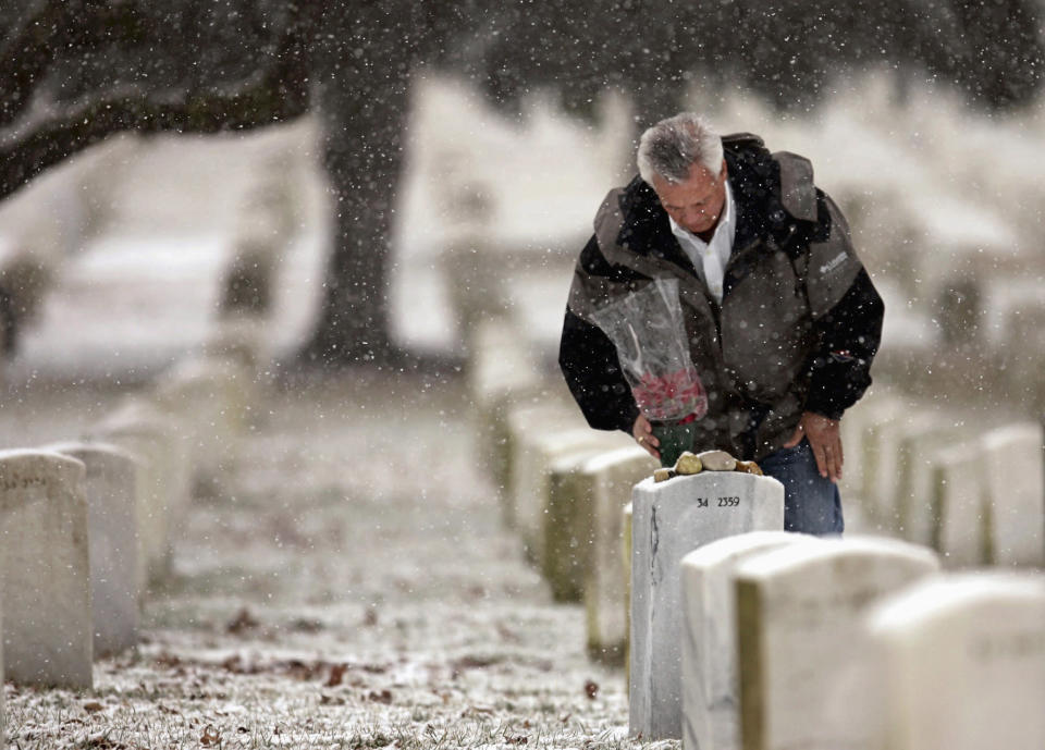 FILE - In this Feb. 28, 2005, file photo, Johnny Spann, father of slain CIA officer Mike Spann of Alabama, who was the first American to die in Afghanistan, pauses at his son's gravesite at Arlington National Cemetery in Arlington, Va. Spann said he is not opposed to Americans leaving Afghanistan but disagrees with the timing and how it was done. (AP Photo/Haraz Ghanbari, File)