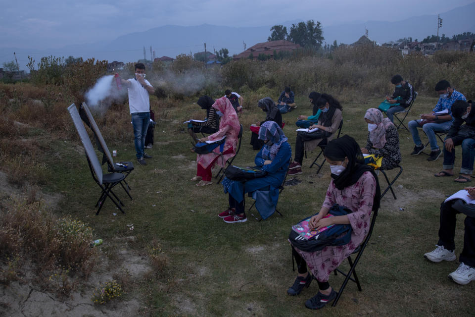Muneer Alam, an engineer-turned-math teacher, sprays disinfectant before the start of an early morning outdoor class at Eidgah, a ground reserved for Eid prayers, in Srinagar, Indian controlled Kashmir, Friday, July 18, 2020. Alam said the driving force to start the open-air classes was seeing children all around him depressed and anxious. The open-air classroom buzzes with students. Some sit on chairs. Others place themselves on rugged mats or on the ground. Social distancing is maintained. (AP Photo/Dar Yasin)