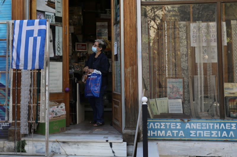 A woman wearing a protective face mask is seen inside a store, amid the spread of the coronavirus disease (COVID-19), in Athens