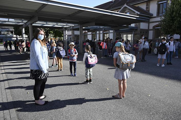 Children line up to enter their classrooms at the Ziegelau elementary school in Strasbourg, France, as primary and middle schools reopen June 22.