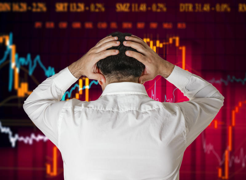 A stock broker panics looking at a falling chart