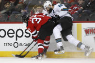 New Jersey Devils center Pavel Zacha (37) checks San Jose Sharks defenseman Brent Burns (88) against the boards during the first period of an NHL hockey game, Thursday, Feb. 20, 2020, in Newark, N.J. (AP Photo/Kathy Willens)