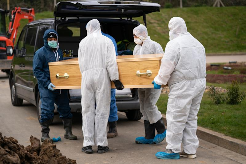 Undertakers in protective gear carry Ismail Mohamed Abdulwahab's coffin after he died of the coronavirus.