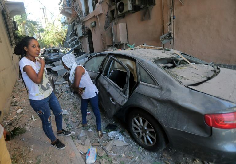 Migrant women walk through the rubble in one of Beirut's heavily damaged neighbourhoods