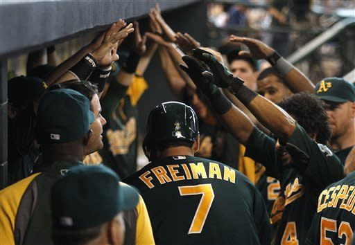 Oakland Athletics' Nate Freiman (7) is congratulated by teammates after hitting a solo home run in the sixth inning during a baseball game against the Houston Astros, Sunday, May 26, 2013, in Houston. (AP Photo/Patric Schneider)