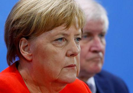 FILE PHOTO: German Chancellor Angela Merkel and Interior Minister Horst Seehofer address a news conference following the so called a housing summit on rising rents in many German cities and a general shortage of affordable housing in Berlin, Germany September 21, 2018. REUTERS/Fabrizio Bensch/File Photo