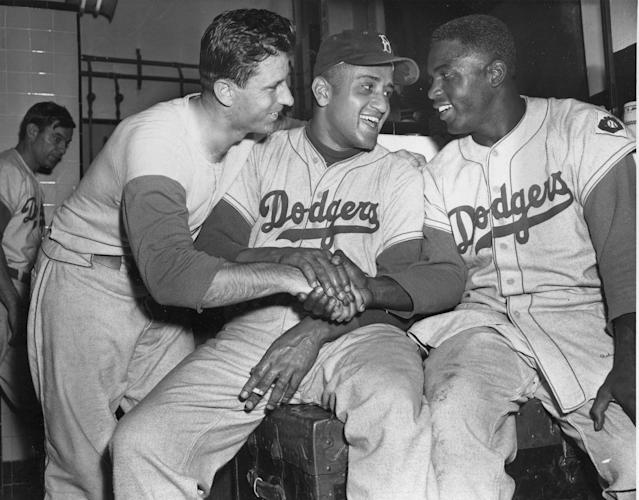 "FILE - In this Sept. 29, 1951 file photo, Brooklyn Dodgers baseball player Andy Pafko, left, Don Newcomb, center, and Jackie Robinson shake hands in their dressing room after the Dodgers beat the Philadelphia Phillies 5-0, in New York. That flowing blue ""Dodgers"" script across the front of the jersey that followed them from Brooklyn. That pointy, ornate ""B"" on the Red Sox cap. Same style, now and then. (AP Photo/File)"