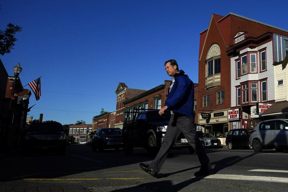 A man walks through downtown Skowhegan, Maine, Tuesday, Sept. 14, 2021. The town has relied on waterpower for its milling industries since the nineteenth century. Conservation groups are advocating for the removal of dams which provide power to a nearby paper mill. (AP Photo/Robert F. Bukaty)