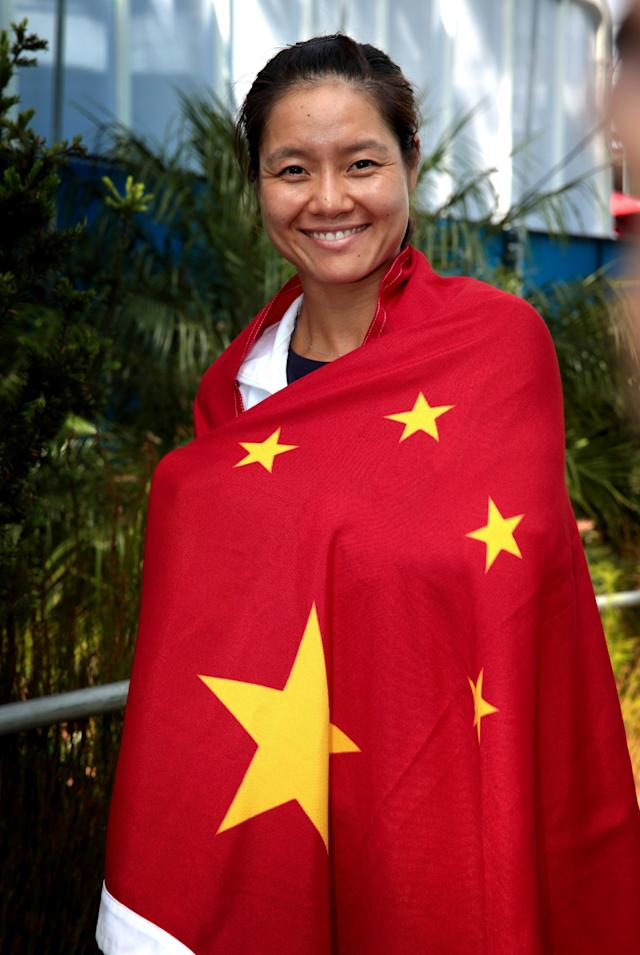 In this photo released by Tennis Australia, Li Na of China poses with a Chinese flag at the Australian Open tennis championship in Melbourne, Australia, Friday, Jan. 24, 2014. Li faces Dominika Cibulkova of Slovakia in the women's singles final Saturday. (AP Photo/Tennis Australia, Fiona Hamilton)