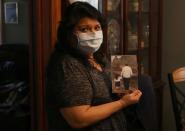 Estela Hernanez, a daughter of longtime JBS USA meat packing plant employee Saul Sanchez, holds a photo of him in Greeley