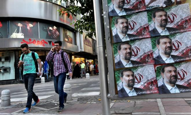 Two men walk past posters of Mohsen Rezaei, one of six presidential candidates hand-picked by the Iranian regime.