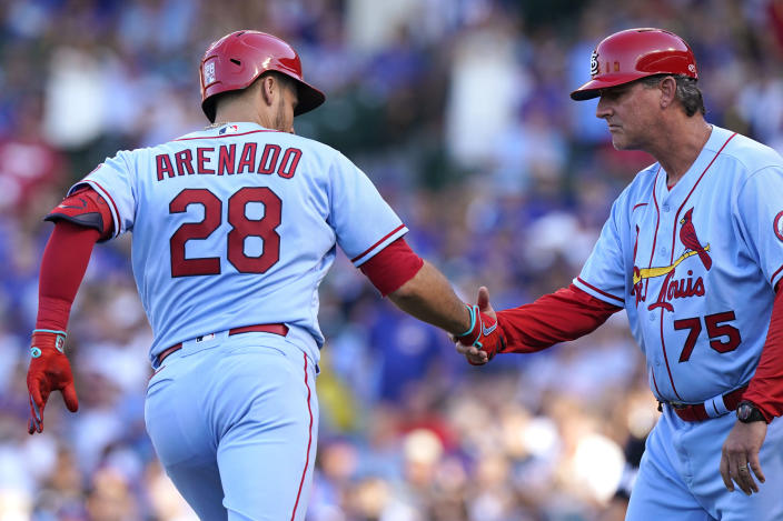St. Louis Cardinals' Nolan Arenado, left, is congratulated by third base coach Ron 'Pop' Warner after hitting a solo home run during the second inning of the team's baseball game against the Chicago Cubs in Chicago, Saturday, June 12, 2021. (AP Photo/Nam Y. Huh)