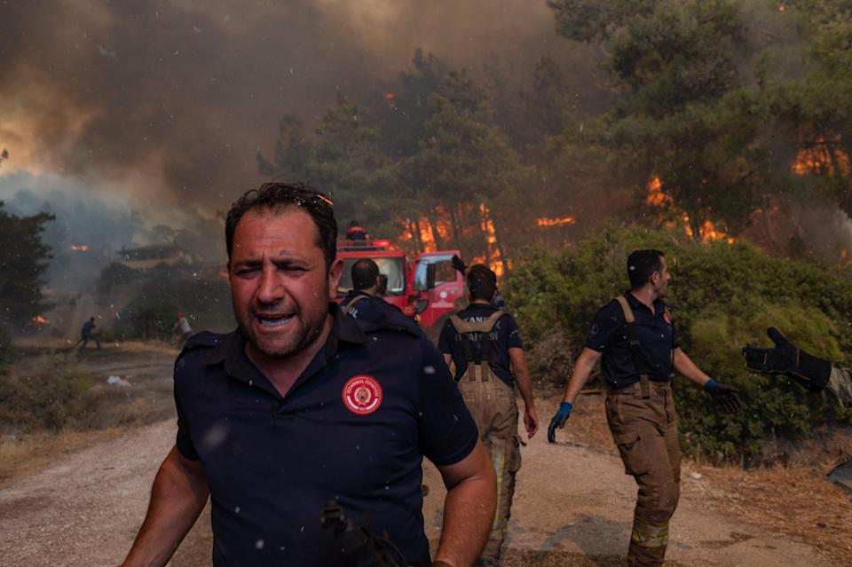 """Firefighters battle a wildfire in Mugla, Marmaris district, Turkey, on Aug. 2. Turkey's struggles against its deadliest wildfires in decades come as a blistering heatwave grips southeastern Europe.<span class=""""copyright"""">Yasin Akgul—AFP/Getty Images</span>"""
