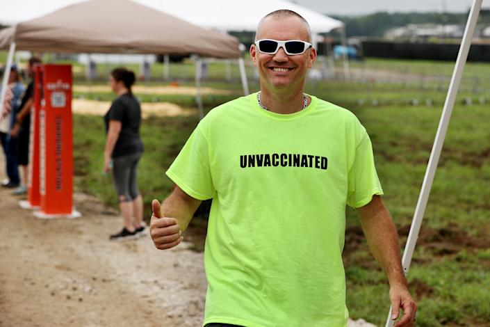 A man wears an 'UNVACCINATED' t-shirt ahead of Donald Trump's