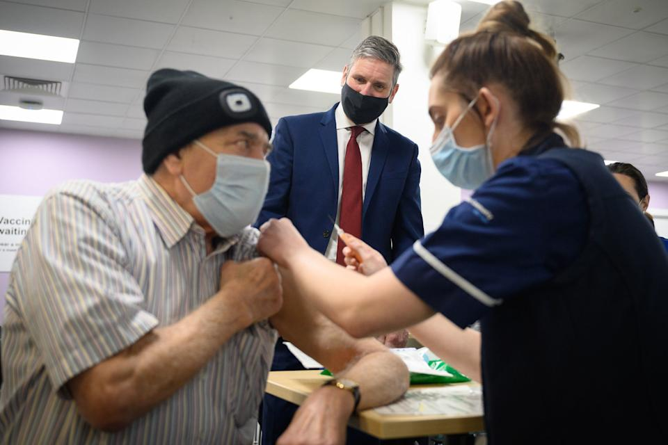 <p>Labour leader Sir Keir Starmer looks on as Melvin Allanson receives the first of two Covid-19 vaccination shots, during a visit to the vaccination centre at Robertson House, in Stevenage.</p> (AFP/Getty)