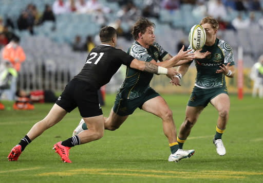 Australia's Michael Hooper, centre, is tackled by New Zealand's T.J. Perenara, left, during the Bledisloe rugby test between the All Blacks and the Wallabies at Stadium Australia, Sydney, Australia, Saturday, Oct. 31, 2020. (AP Photo/Rick Rycroft)