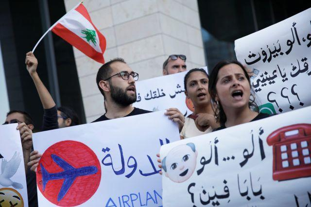 Demonstrators carry banners and a Lebanese flag as they protest outside the Touch telecommunications building in Beirut, Lebanon November 5, 2019.