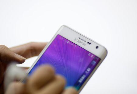 A man tries out a Samsung Electronics' Galaxy Note Edge during the 2014 Korea Electronics Show in Goyang October 17, 2014. Samsung Electronics Co Ltd said third-quarter profit fell 60.1 percent from a year earlier to the lowest in more than three years, as earnings for the mobile division continued to shrink. Picture taken October 17, 2014. REUTERS/Kim Hong-Ji (SOUTH KOREA - Tags: BUSINESS TELECOMS SCIENCE TECHNOLOGY)