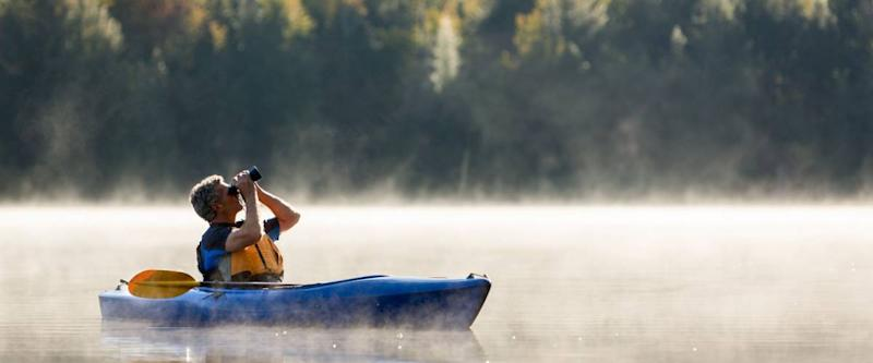 Senior man solo traveller birdwatching from kayak in morning fog