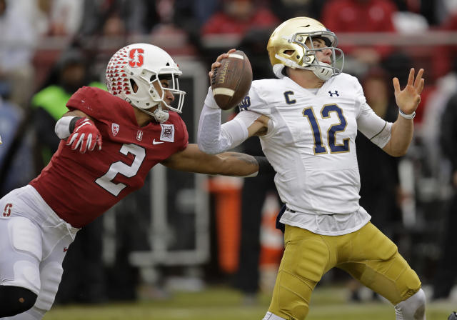 Stanford's Curtis Robinson, left, pressures Notre Dame quarterback Ian Book (12) in the first half of an NCAA college football game Saturday, Nov. 30, 2019, in Stanford, Calif. (AP Photo/Ben Margot)