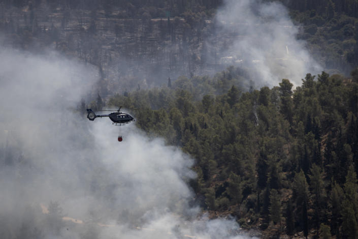 An Israeli helicopter drops water while battling the second day of wildfires near Shoresh, on the outskirts of Jerusalem, Monday, Aug. 16, 2021. Israel Fire and Rescue service said in a statement on Monday, that 45 firefighting teams accompanied by eight planes were working to contain five fires in the forested hills west of the city. (AP Photo/Maya Alleruzzo)