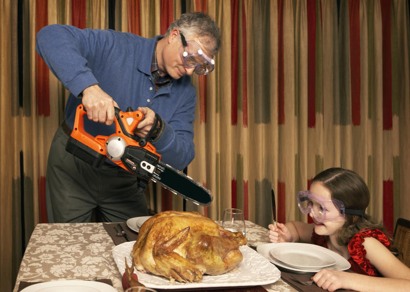 Girl (8-9) watching father cutting turkey using chainsaw at dining room table