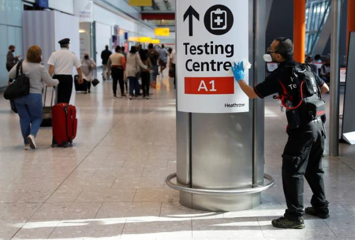 FILE PHOTO: A worker sanitises a sign at the International arrivals area of Terminal 5 in London's Heathrow Airport