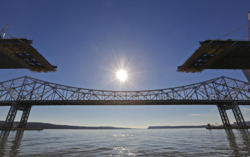 FILE - This Tuesday, Dec. 20, 2016, file photo shows the old Tappan Zee Bridge, background, during construction of its replacement, the Gov. Mario M. Cuomo Bridge, foreground, in Tarrytown, N.Y. Panels from the old bridge will soon be carrying a few dozen cars, pickup trucks and farm tractors over meandering streams after several counties requested salvaging some of the about 150 50-foot-long deck panels. (AP Photo/Seth Wenig, File)