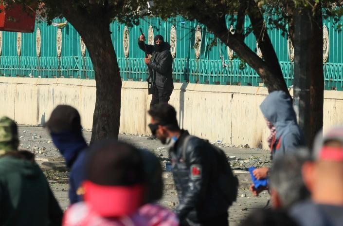 A police officer carries a pellet air rifle during clashes with anti-government protesters in Baghdad, Iraq, Friday, Jan. 31, 2020. (AP Photo/Hadi Mizban)